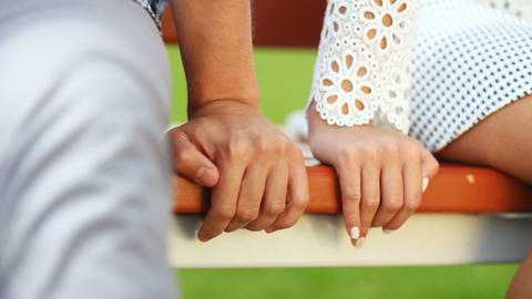 young couple in white sits on park bench at date Stock Video Footage