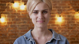 Young attractive short hair hipster girl is watching at camera, smiling, brick Footage