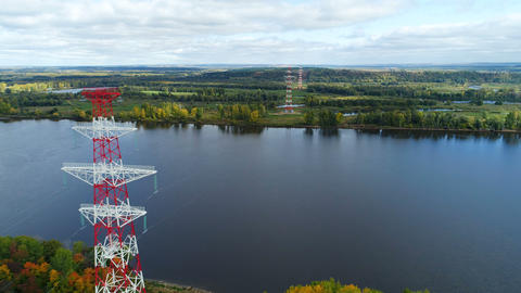 electrical towers located near peaceful river against landscape Footage