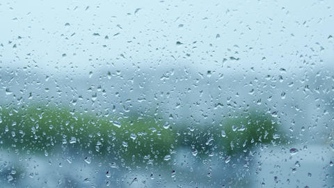 Raindrops on transparent window glass during rain on blurred background Footage