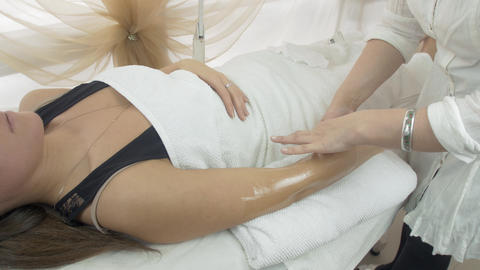 Adult cosmetologist epilate girl hand by wax strip in beauty saloon. Medium shot Live Action
