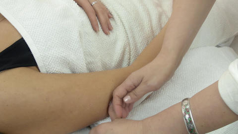 Close up cosmetologist waxing girl hand by strip in beauty saloon. Medium shot Live Action