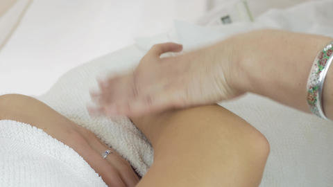 Close up cosmetologist hands waxing right girl hand in beauty saloon. Epilation Live Action