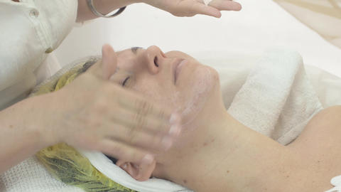 Cosmetologist smear moisturizing cream on woman face in beauty saloon. Skincare Live Action
