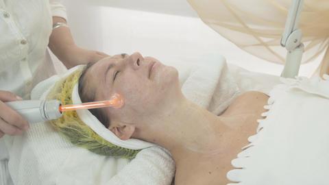 Cosmetologist use darsonval on woman face in beauty saloon. Moiston cream Footage