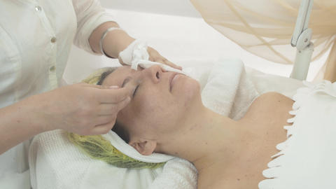 Professional beautician put napkins on woman face to get wet in saloon. Skincare Live Action