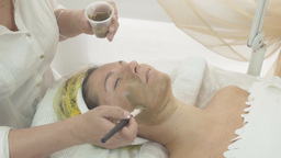 Cosmetologist put mask made of green clay on woman face in beauty saloon Footage