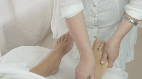 Masseuse make massage of right foot to woman in saloon. Skincare. Therapy Live Action