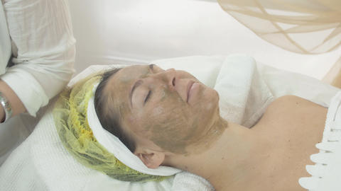Girl face with green clay cosmetic mask in beauty saloon. Skincare. Cosmetology Live Action