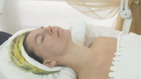 Woman face with closed eyes in beauty saloon on cosmetic procedure. Problem skin Footage