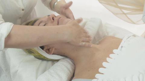 Cosmetologist smear bit moisten cream on woman neck in beauty saloon. Skincare Live Action