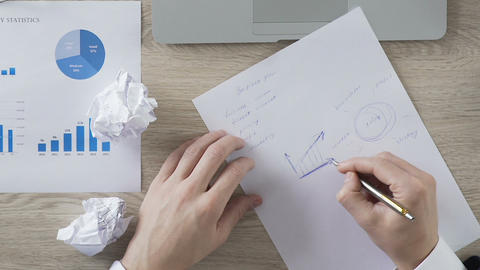Businessman drawing graph on piece of paper and balling it up, crisis, problems Footage