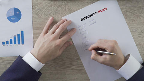 Entrepreneur writing down company business plan, entrepreneurship, start-up Footage
