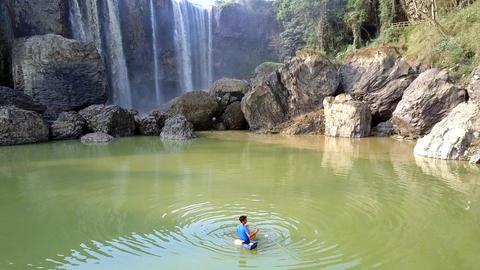 fisherman pulls net in quiet lake against waterfall Footage