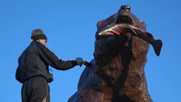 Worker paints sculpture of Kamchatka brown bear with salmon in mouth Footage
