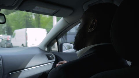 Business man riding in car with personal driver, solving problems by phone Live Action
