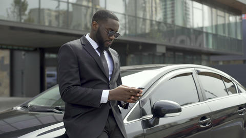 Rich Afro-American man waiting for partners near office building to do business Live Action