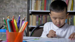 Young little asian boy painting on paper and sitting behind table, kid doing Footage
