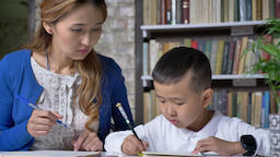 Asian little boy doing homework with young mother, women helping kid, sitting Footage