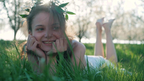 Beauty Smiling Girl lying on the Spring Meadow with wild Flowers. Laughing And Footage