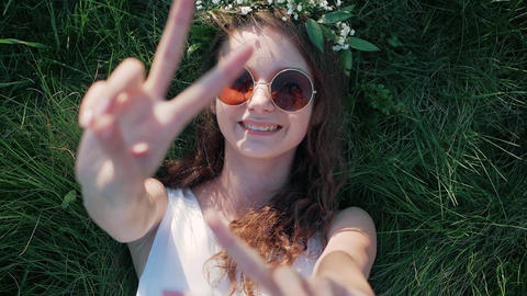 SLOW MOTION: Top view shot of a Caucasian girl in a white floral dress lying in Footage
