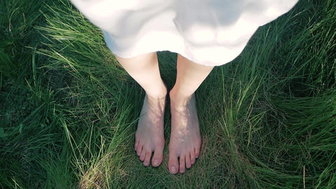 The girl is barefoot on her green grass. The wind waves a white dress Footage