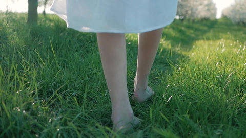 Slow motion shot of bare feet of young girl walking and running on green grass Live影片