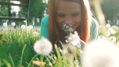 Beauty Girl lying on dandelions meadow and smelling flowers. Beautiful Spring Footage