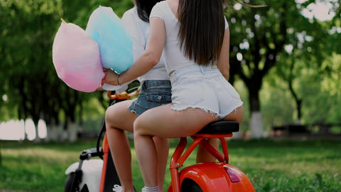 Two young and sexy brunette friends with loose hair in short denim shorts riding Live Action