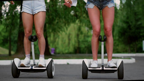 Two sexy young girls riding on Segway in short shorts holding hands and laughing Live Action