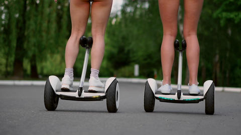 Close-up view of the back legs of the girls in short shorts riding GyroScooter Live Action
