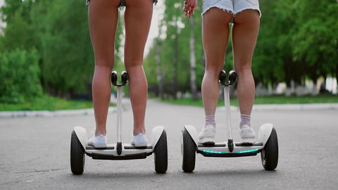 Sexy girls in short denim shorts ride on white Segways close - up slow motion Live Action