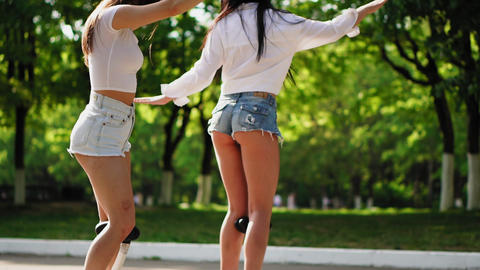 Two girls in white t-shirts and denim shorts laughing while walking in the Park Footage