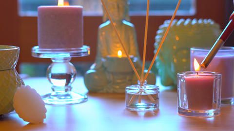 Aromatherapy table setting with perfumed candles, oil burner, buddhas, and mood Footage