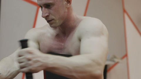 A muscular man with a naked torso trains on a fitness machine in a fitness club Footage