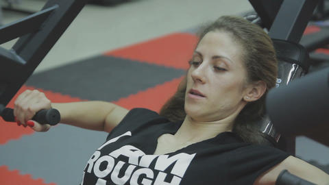 Very beautiful female trainer trains on a fitness machine in a fitness club Footage