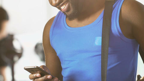 Young male standing in gym with bag on shoulder, reading message on cellphone Footage