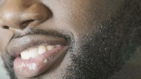 Black guy smiling to camera with charming smile, white teeth, super close-up Footage