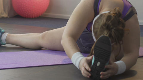 Overweight girl doing stretching exercises for legs on floor, muscles workout Footage