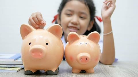 Asian little girl in Thai student uniform putting coin in to piggy bank shallow depth of field GIF
