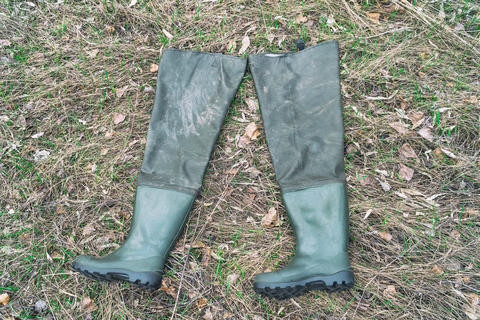Boots for fishing on dry grass Photo