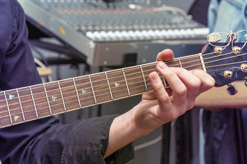 The hand of the guitarist on fingerboard Photo