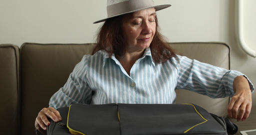 Elderly woman is going on vacation packing a suitcase Footage