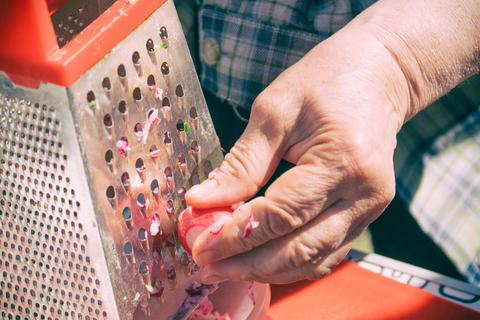 Woman rubs vegetables on a grater フォト
