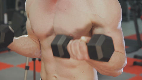 A man is training with dumbbells in the gym Footage
