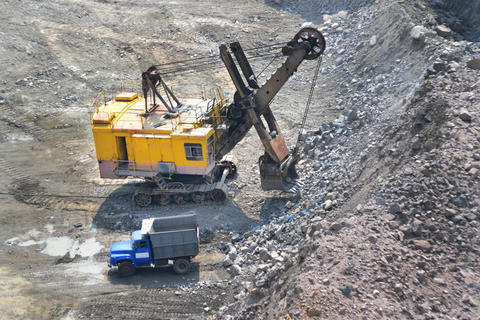 huge excavator and a truck on granite quarry Photo