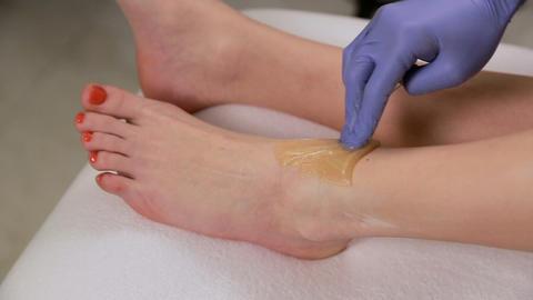 Sugar paste, shugaring cosmetic procedures depilation. Smooth skin legs Live Action
