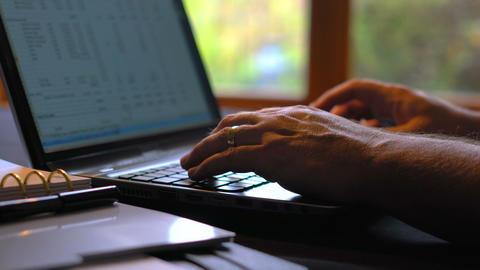4k Man entering figures in spreadsheet on laptop screen, indoors in low light, Live Action