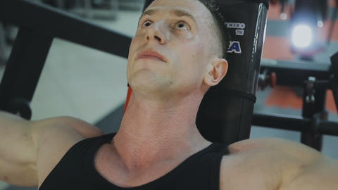 A muscular man in a black T-shirt is training on a fitness machine in a fitness Live Action