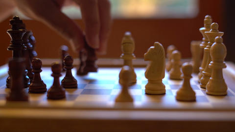Chess game, male and female taking knights, in natural window light, shallow DOF Footage